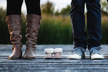 Family Planning - Baby Shoes And Parents Outdoors