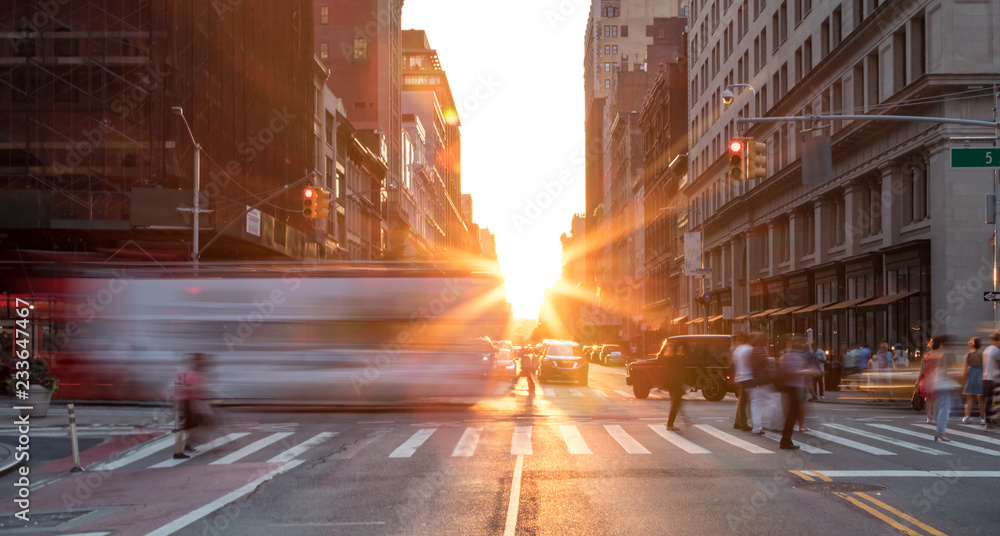 Fototapeta Busy New York City street scene with crowds of people in Midtown Manhattan with sunset background