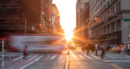 Busy New York City street scene with crowds of people in Midtown Manhattan with sunset background