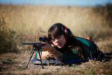 Woman Aiming Through Rifle While Lying On Front In Field