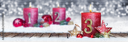 Dritter Advent schnee panorama Kerze mit Zahl dekoriert weihnachten Aventszeit holz hintergrund lichter bokeh / third sunday advent