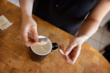 Midsection Of Woman Holding Teabag Over Mug At Kitchen Counter