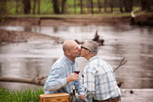 Gay Couple Kissing While Sitting By Lake