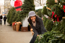 Cheerful Woman Pulling Christmas Tree In Market
