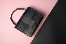 Top View Of Stylish Little Black Bag On Baby Pink And Black Background.