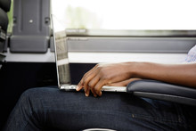 Cropped Image Of Man Using Laptop Computer While Sitting In Bus
