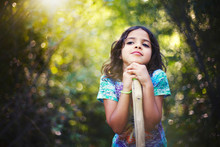 Thoughtful Girl Leaning On Wood In Forest