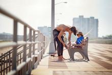Man Wearing Shoes To Boy Sitting At Bench On Bridge
