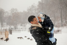Happy Father Carrying Son On Snow Field