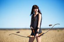 Woman Looking Away While Holding Bow And Arrow On Field