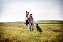 Portrait Of Woman With Horse And Dog Standing On Field Against Sky