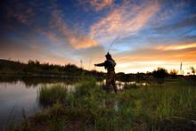 Rear View Of Man Fishing In La...