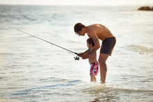 Side View Of Father Teaching Fishing To Son While Standing In Water At Beach