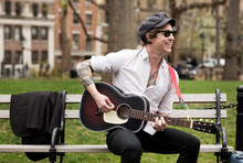 Street Musician Playing Guitar While Sitting On Bench At Park