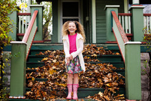 Portrait Of Happy Girl Standing On Steps During Autumn