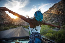 Rear View Of Woman Enjoying In Car On Mountain Road During Sunset
