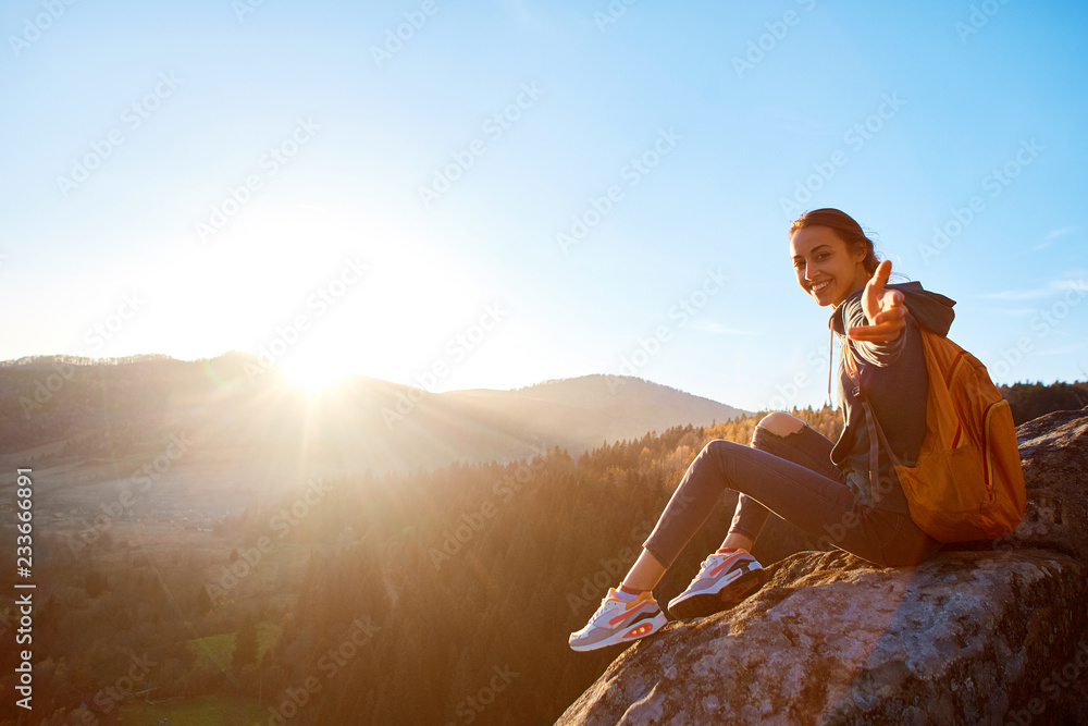 Fototapety, obrazy: first view of woman hiker with backpack sits on edge of cliff against background of sunrise and extends a hand