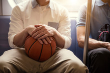 Midsection Of Man Holding Basketball While Traveling With Friend In Train