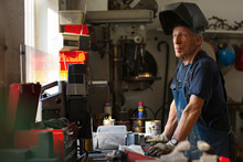 Senior Man Looking Away While Standing By Workbench In Workshop