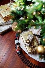 High Angle View Of Christmas Presents And Miniature Train On Hardwood Floor