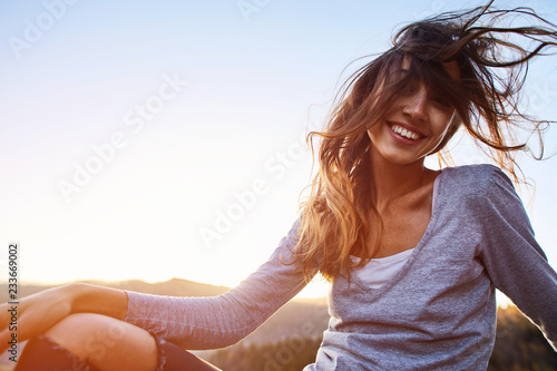 Stampa su Tela portrait of smiling cheerful woman with long hair sitting on edge of cliff against background of sunrise