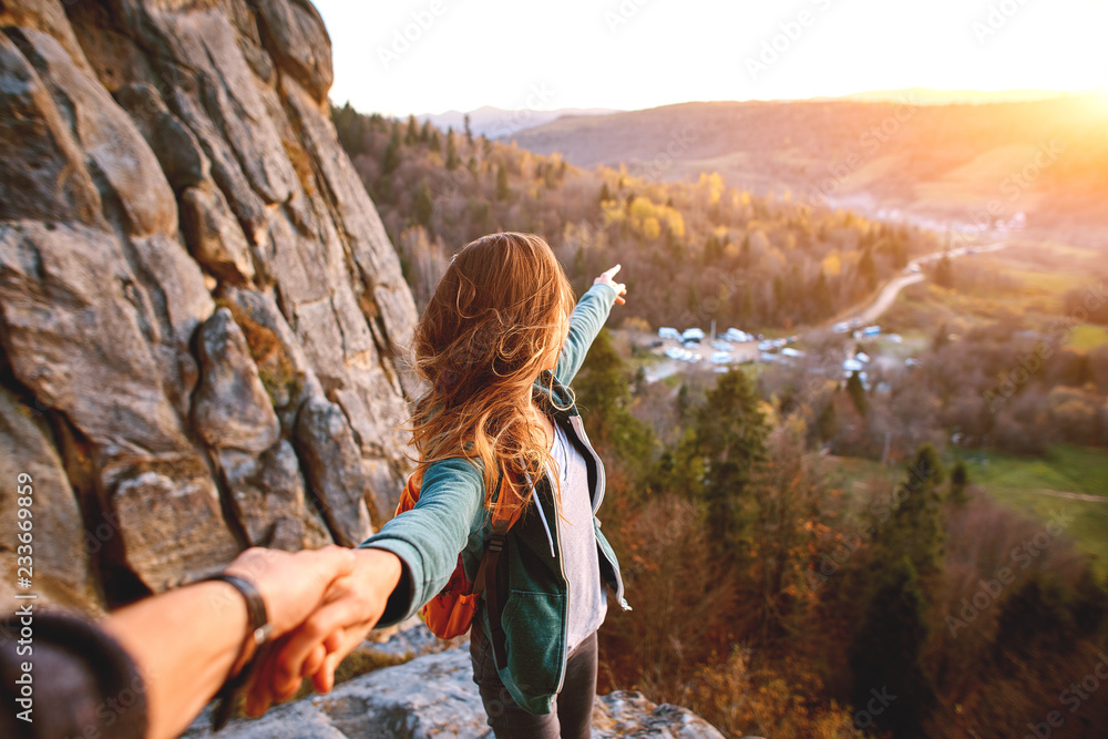 Fototapety, obrazy: first view of woman hiker with backpack stands on edge of cliff against background of sunrise and extends a hand