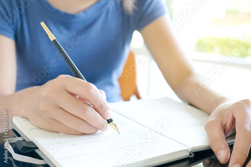 Fotografía Woman's hand Writing in the notebook In the living room, the concept of education and work