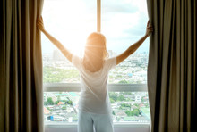 Morning Of A New Day Woman Wake Up In The Bedroom With Her Refreshing. She Stand At The Window , Raised Her Two Arms And Look City View Get Sunlight
