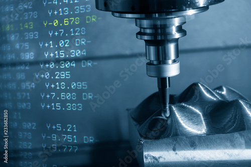 Photo The abstract scene of  CNC milling machine and the NC-code data cutting the mold part