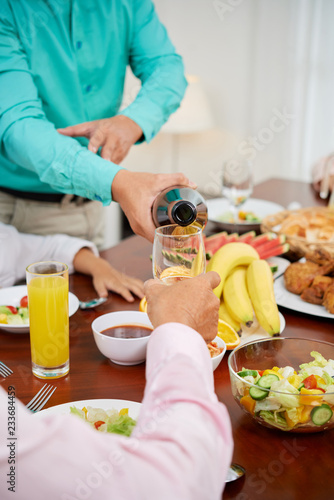 Aluminium Prints Picnic Man filling wine glass of guest at dinner table
