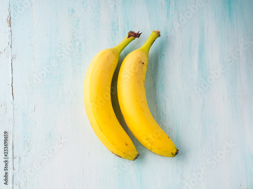 Two bananas on green pastel background. Food flat lay concept