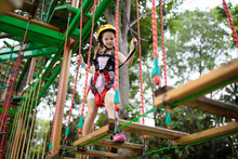 Child In Adventure Park. Kids Climbing Rope Trail.