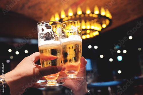 Fototapeta Couple or Friend making Cheers with a Glass of Beer to Celebrate in Restaurant,B