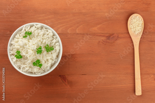 A photo of a bowl of cooked white long rice and a spoon of the same dry rice, shot from the top on a rustic background with copy space