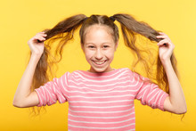 Happy Joyful Smiling Adolescent Girl Showing Her Pig Tails Relaxed Carefree Lifestyle And Childish Behavior.