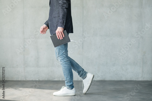 business man walking holding notebook in hand. smart casual fashion style