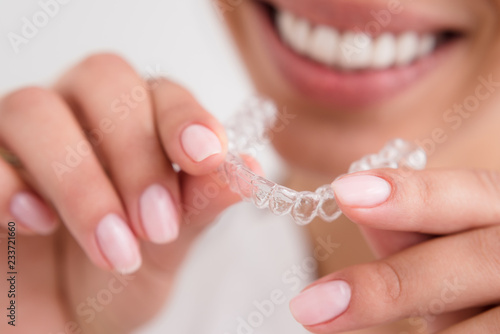 Fotografia  girl with a beautiful smile holding a transparent mouth guard