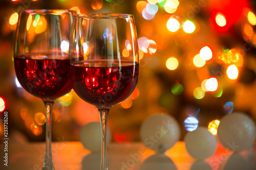 Glasses of wine and Christmas balls on the background of Christmas lights