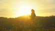 Silhouette of hiker tourist woman with backpack trekking on mountain at sunset. Hiker girl. Female traveler woman enjoying vacation travel in beautiful landscape nature outdoors. Sun lens flare. slow