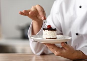 Muški kuhar s ukusnim desertom u kuhinji, izbliza