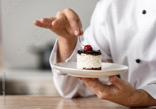 Photo  Male chef with tasty dessert in kitchen, closeup
