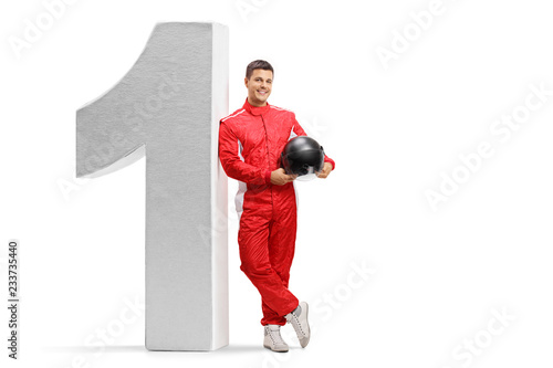 Racer leaning against big sized number one and holding a helmet