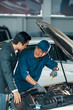 Smiling Asian worker in uniform fixing the car and explaining the operation of the engine to the client in car service