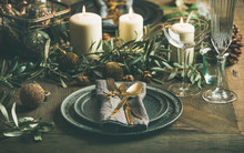Christmas Or New Years Celebration Party Table Setting. Plates, Golden Cutlery, Glasses, Festive Branch Decoration, Candles And Gliterring Toys Over Rustic Wooden Table Background