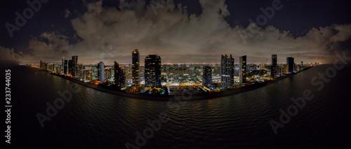 Cuadros en Lienzo Aerial night drone panoramac photo coastal city highrise tower illuminated