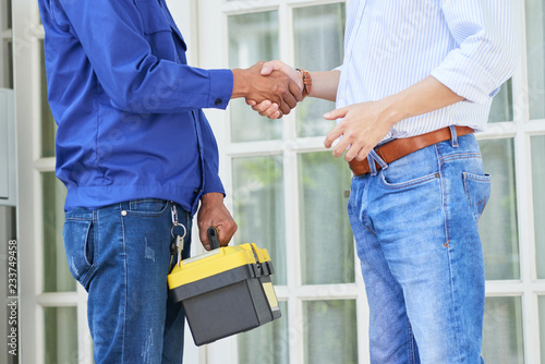 Man thanks the repairman for the good work and shaking hands with him opposite the door of his house