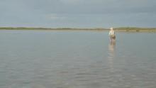 Man Wading In A Flat Lagoon Fishing For Bonefish