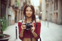 Attractive Tourist Woman Photographer With Dslr Camera Looking At Camera Outdoor In City Street In Barcelona, Spain. Gorgeous Happy Mixed Race Asian Caucasian Female In Casual Hipster Clothes With