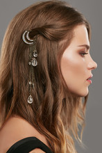 Close Up Portrait Of A Young Brunette Lady With Natural Make-up And Wavy Hairstyle. Her Tresses Are Adorned With Bronze Half Moon Hair Clip. The Side View Of The Girl Posing Over The Grey Background.