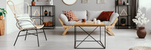 Wood And Metal Coffee Table With Candles And Tea Cup In Bright Living Room Interior With Grey Lounge With Cushions And Chair, Metal Racks With Decor And Plant In Vase In Real Photo